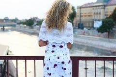 Gelocktes blondes Mädchen, das auf der Brücke steht und ein weißes Sca hält Stockbilder