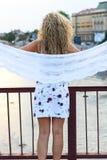 Gelocktes blondes Mädchen, das auf der Brücke steht und ein weißes Sca hält Stockfotos