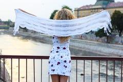 Gelocktes blondes Mädchen, das auf der Brücke steht und ein weißes Sca hält Lizenzfreies Stockfoto