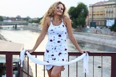 Gelocktes blondes Mädchen, das auf der Brücke steht und ein weißes Sca hält Lizenzfreie Stockfotos
