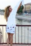 Gelocktes blondes Mädchen, das auf der Brücke steht und mit einem Weiß wellenartig bewegt Lizenzfreie Stockfotos
