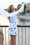 Gelocktes blondes Mädchen, das auf der Brücke steht und mit einem Weiß wellenartig bewegt Stockfotografie