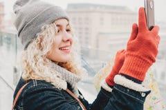 Gelocktes blondes Mädchen, das selfie oder Foto macht Stockfotos