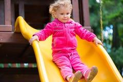 Gelocktes blondes Mädchen, das am Spielplatz schiebt Lizenzfreies Stockfoto