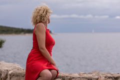 Gelocktes blondes Mädchen im roten Kleid nahe des Meeres Stockbild