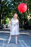 Gelocktes blondes Mädchen mit großem rotem Ballon Stockfoto