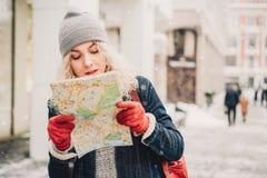Gelocktes blondes Mädchen mit Karte, Winter stockfotografie