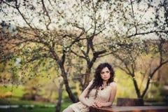 Gelocktes Brunettemädchen, das in blühenden Bäumen steht stockfoto