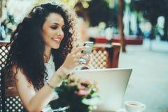 Gelocktes Brunettemädchen im Café mit Smartphone und Laptop Stockfoto