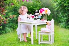 Gelocktes entzückendes Kleinkindmädchen, das Teeparty mit Puppe spielt Lizenzfreies Stockbild