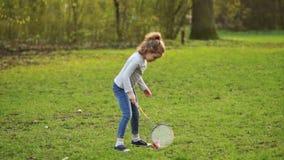 Gelocktes hübsches Mädchen, das Badminton im Park spielt stock footage