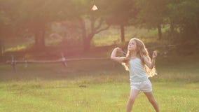 Gelocktes hübsches Mädchen, das Badminton im Park spielt Langsame Bewegung stock video footage
