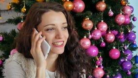 Gelocktes junges Mädchen, das an einem Handy auf dem Hintergrund eines kreativ verzierten Weihnachtsbaums spricht stock footage