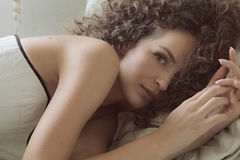 Gelocktes junges schönes Mädchen liegt auf einem Bett in einem weißen Korsett und dem Betrachten der Kamera Stockbild