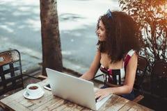 Gelocktes kaukasisches Mädchen mit dem netbook in einer Straßenstange lizenzfreie stockfotografie