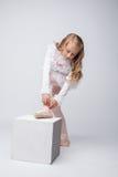 Gelocktes kleines Mädchen, das pointe, auf grauem Hintergrund bindet Stockfoto