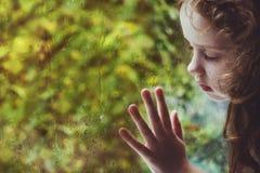 Gelocktes kleines Mädchen, welches heraus das Regentropfenfenster schaut stockfotografie