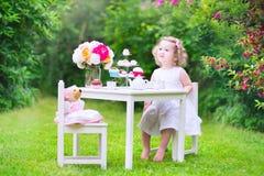 Gelocktes Kleinkindmädchen, das Teeparty mit einer Puppe spielt Lizenzfreie Stockfotos