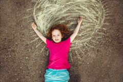 Gelocktes Mädchen, das auf Asphalt mit gemalter gelber Sonne liegt Lizenzfreies Stockfoto