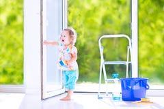 Gelocktes Mädchen, das ein Fenster im Reinraum wäscht Stockbild