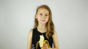 Gelocktes Mädchen, das eine Banane auf einem weißen Hintergrund isst stock video footage