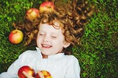 Gelocktes Mädchen liegt auf dem Gras mit Apfel und dem Lächeln Stockfotos