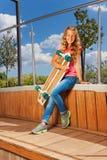 Gelocktes Mädchen mit Skateboard sitzt im Park Stockfotos