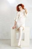 Gelocktes Mädchen der Rothaarigen in einem Weiß strickte Strickjacke und Strümpfe sitt Stockfotos