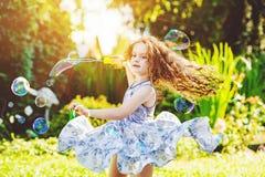 Gelocktes Mädchen im Fliegenkleid, das mit Seifenblasen spielt Stockfotos