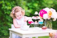 Gelocktes nettes Kleinkindmädchen, das Teeparty mit einer Puppe spielt Stockfotografie