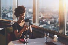 Gelocktes schwarzes Mädchen, das selfie im caffee macht Stockfotografie