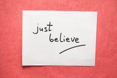 Geloof enkel - tekst op papier met roze concept als achtergrond, godsdienst en geloofs stock foto