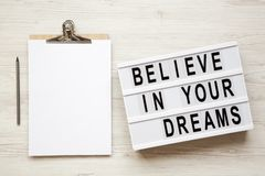 ` Geloof in uw dromen` woord op moderne raad, noticeboard, potlood over witte houten achtergrond, overheadkosten De hoogste vlakk royalty-vrije stock foto's