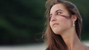 Gelooid gezicht van een charmant jong meisje met lang haar, dat sensually op de camera in de avond op de kust stelt stock video