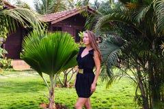 Gelooid meisje op de achtergrond van een palmbos Stock Afbeelding
