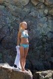 Gelooide blonde haired vrouwelijke persoon die op afgezonderde plaats van wilde rotsachtige kust rusten stock afbeelding