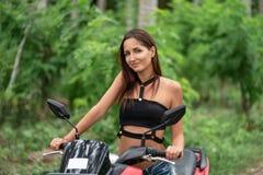 Gelooide, jonge vrouw met een glimlach stellende zitting op een motorfiets stock afbeelding