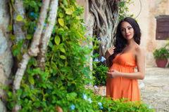 Gelooide zwangere meisjestoerist in een heldere kleding dichtbij tropische lianas en oude steengebouwen van het dorp Royalty-vrije Stock Foto