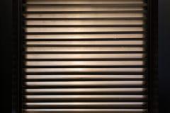 Gelosia sulla finestra Bande di luce È interno scuro Fotografie Stock