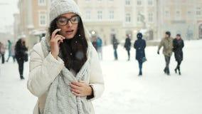 Geluk, de wintervakantie, Kerstmis, dranken en mensenconcept - gelukkig meisje die op de de sneeuwwinter van de telefoonstad spre stock videobeelden