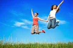 Geluk het jonge vrouwen springen Stock Foto's
