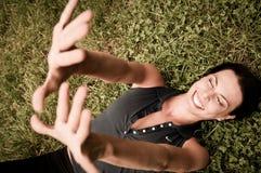 Geluk - vrouw die in gras ligt Stock Afbeelding
