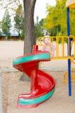 Gelukkig aanbiddelijk kindmeisje op schommeling op speelplaats dichtbij kleuterschool Montessori op de zomerdag Stock Foto's