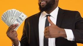 Gelukkig Afrikaans-Amerikaans mannetje in kostuum die bos van dollars en duimen tonen stock footage