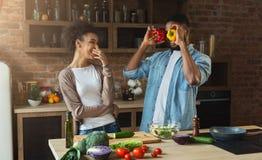 Gelukkig Afrikaans-Amerikaans paar die en pret in keuken koken hebben stock foto