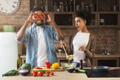 Gelukkig Afrikaans-Amerikaans paar die en pret koken hebben stock foto's
