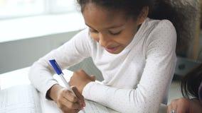 Gelukkig Afrikaans Amerikaans studentenmeisje die thuis ernstig onderwijs leren en thuiswerk samen met vrouwelijke school doen stock video