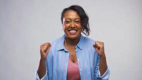 Gelukkig Afrikaans Amerikaans vrouw het vieren succes stock video