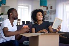 Gelukkig Afrikaans paar die pret uitpakkende dozen in woonkamer hebben royalty-vrije stock afbeeldingen