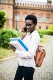 Gelukkig Afrikaans universiteitsmeisje die op mobiele telefoon spreken Jong meisje die op telefoon bij pauze in Uni spreken royalty-vrije stock afbeeldingen